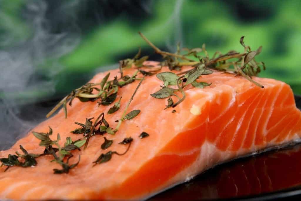 Imagem de um pedaço de salmão fresco e sobre ele alguns ramos de erva para tempero.
