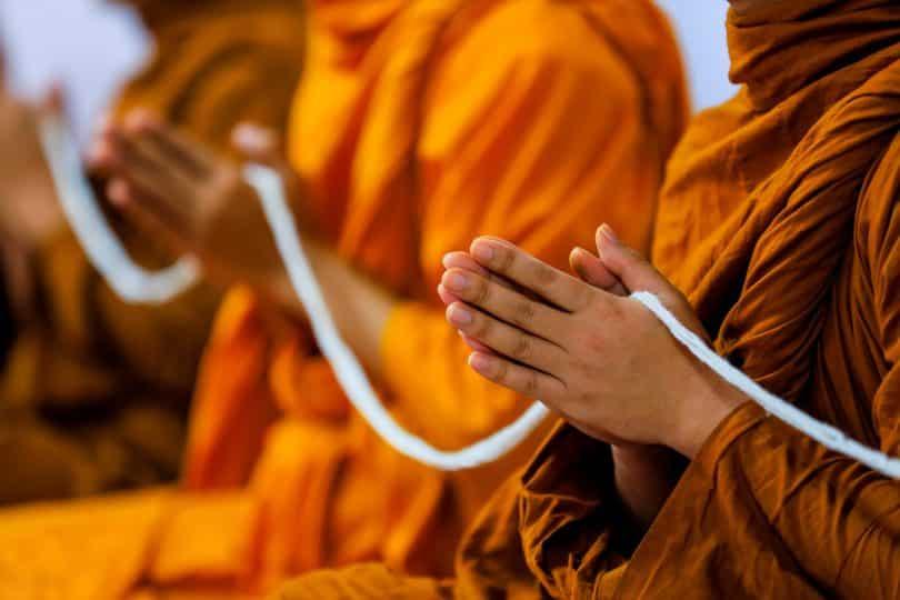 Homens usando roupas laranjas e com mãos juntas segurando linha branca.