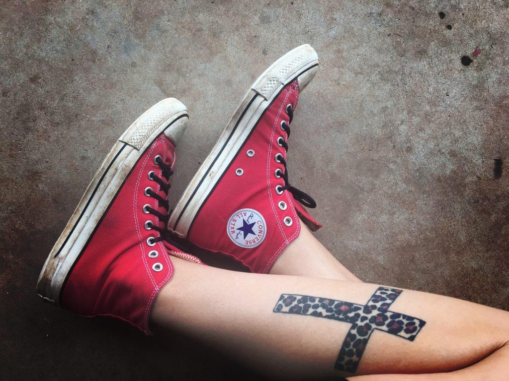 Imagem das penas de uma mulher e em uma delas está a tatuagem de uma cruz.