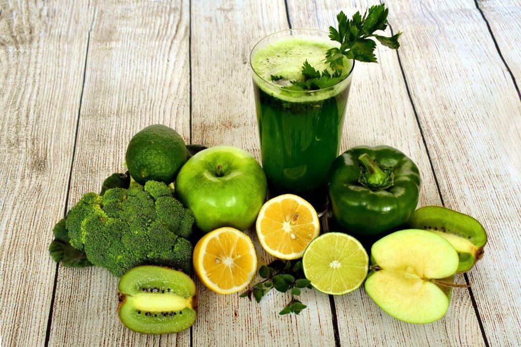 Imagem de um copo contendo suco detox verde. O copo é decorado com salsinha e ao lado vários legumes, frutas e verduras verde, utilizados para o preparo do mesmo.