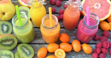 Imagem de várias garrafas contendo diversos tipos de sucos detox feitos com ingredientes amarelos,, verdes e vermelhos, que ajudam no processo de desintoxicação alimentar.
