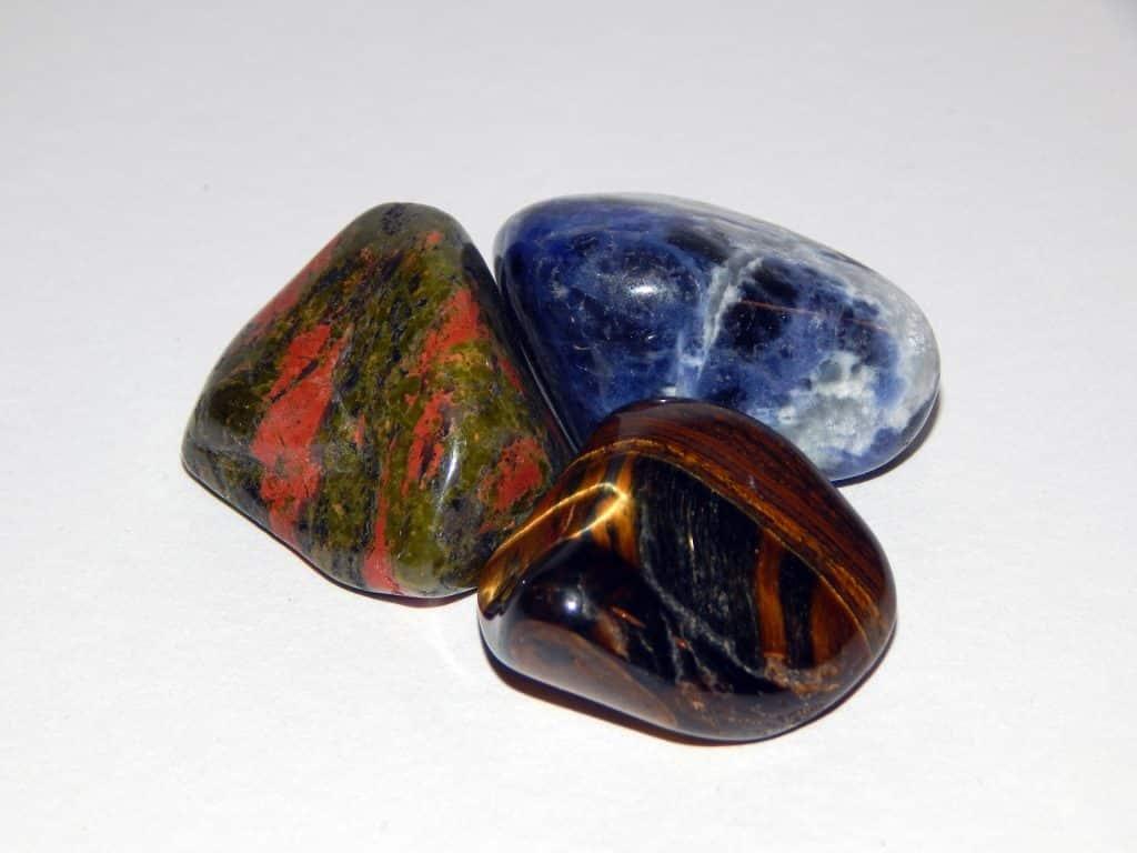 Imagem de três pedras de olho de tigre com cores diferentes.