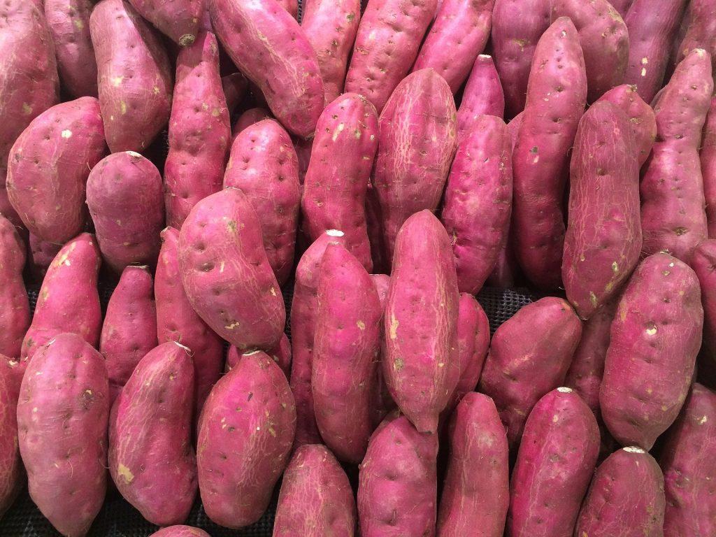 Imagem de uma bancada de feira contendo muitas batatas doces da cor roxa.