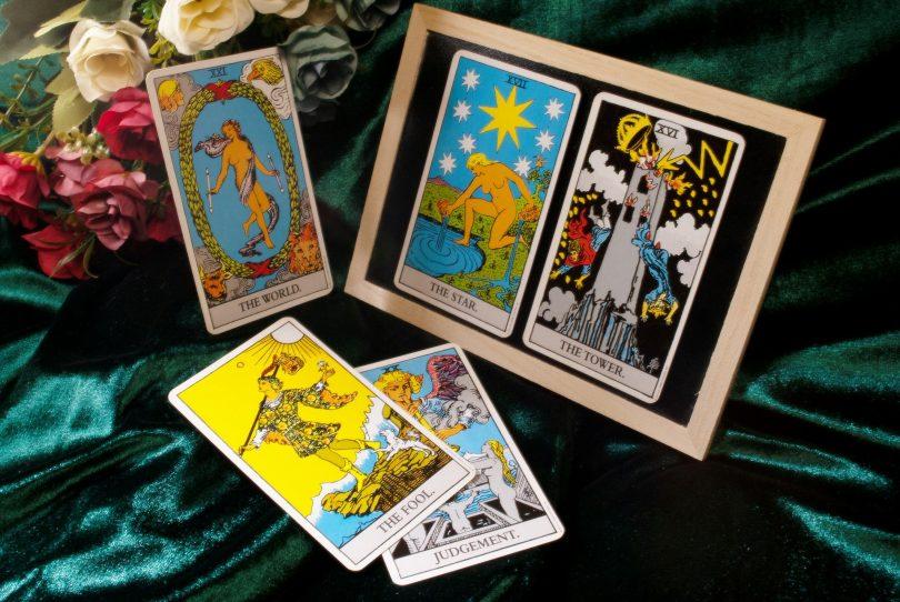Imagem de uma mesa com cinco cartas de tarot dispostas sobre um pano verde brilhante. Ao lado um vaso com rosas coloridas.
