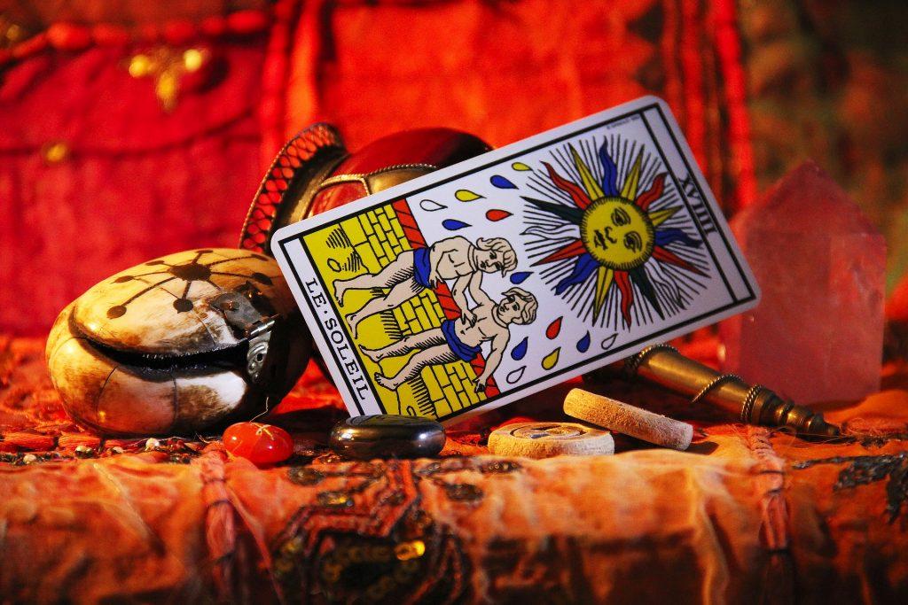 Imagem da carta de tarot Sol disposta sobre uma mesa forrada com uma toalha alaranjada e decorada com vários tipos de pedras e cristais.