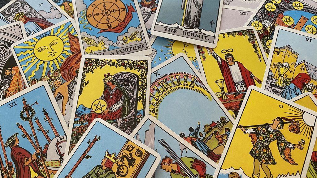 Imagem de várias cartas de tarot nas cores azul, amarelo e branco.