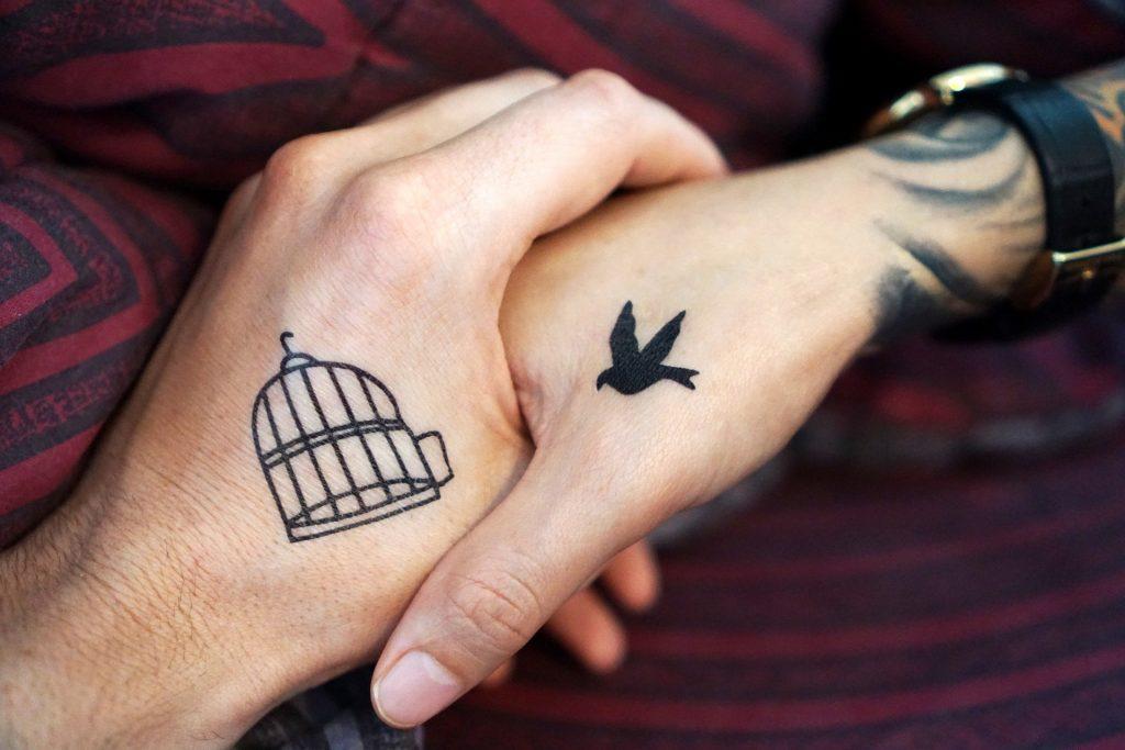 Imagem de duas mãos tatuadas. Em uma delas está a figura de uma gaiola e na outra de um pássaro voando.