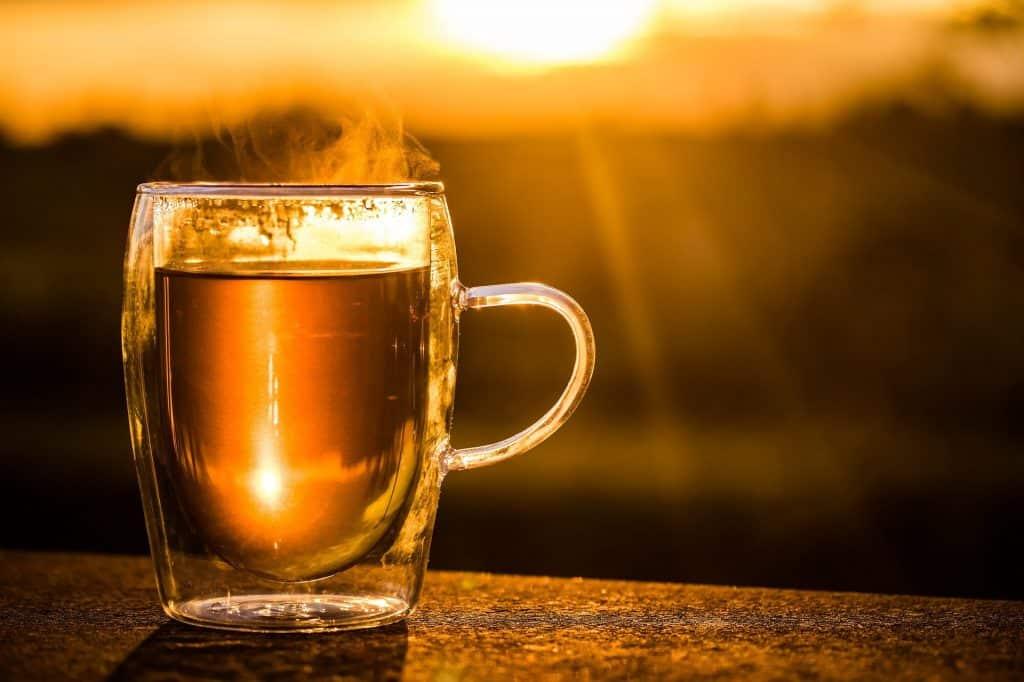 Imagem de uma caneca grande de vidro contendo chá de cavalinha que é bom para ajudar na desintoxicação alimentar.