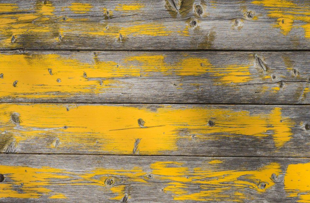 Imagem de uma parede feita de madeira e sobre ela uma textura pintada na cor amarela.