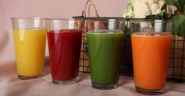 Imagem de quatro copos contendo vários tipos de sucos detox. Ao lado dele um cesto com ingredientes como: frutas e legumes, utilizados para o preparo dos mesmos.