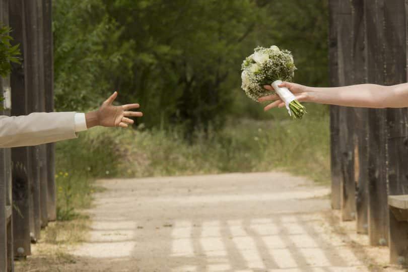 Imagem de uma passarela cercada. De um lado as mãos de um homem e do outro de uma mulher que segura um ramalhete de flor. Eles estão separados.