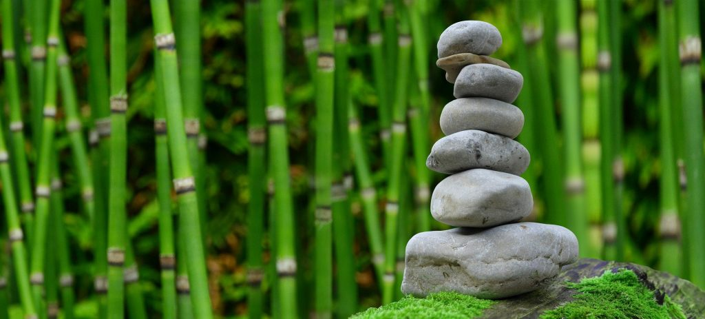Imagem de um lindo jardim zen feito com bambus e várias pedras de tamanhos diversificados, feito para meditar.