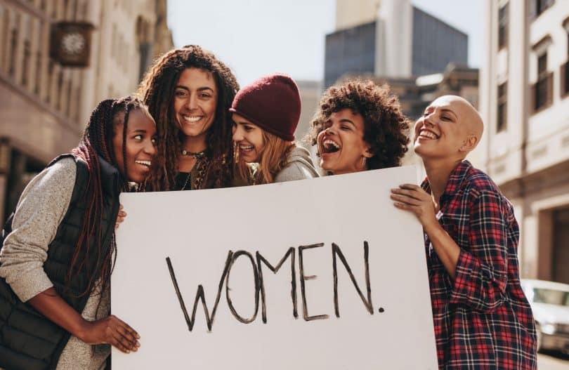 """Mulheres com expressões sorridentes segurando cartaz com a palavra """"women""""."""