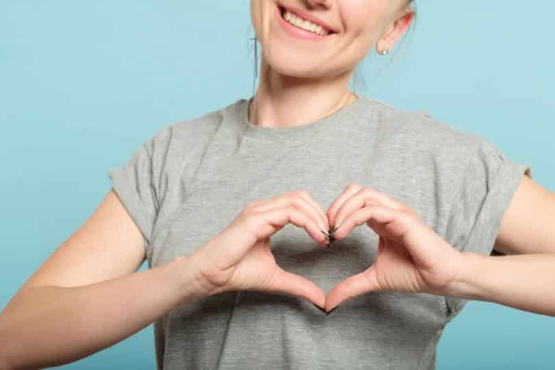 Menina fazendo sinal de coração com a mão