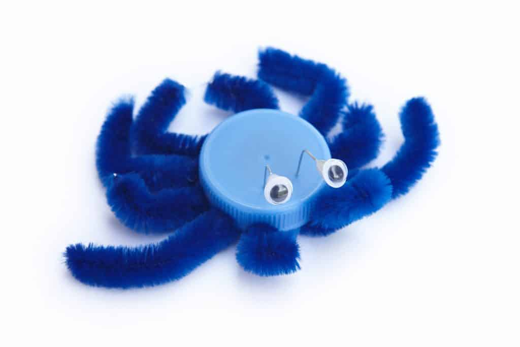 Imagem de um brinquedo reciclado feito de tampinha. É um inseto (aranha) na cor azul.