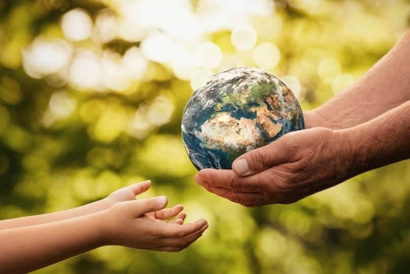 mãos de idoso dando o pequeno planeta Terra para uma criança sobre um fundo verde desfocado