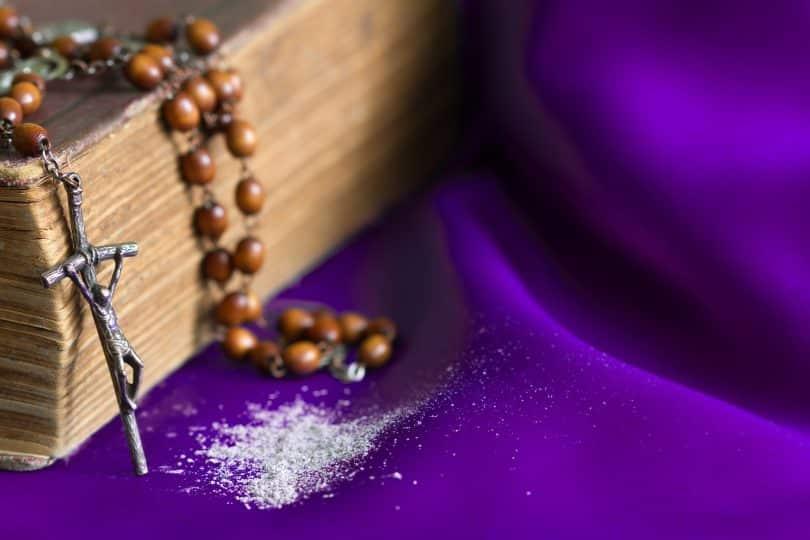 Imagem de uma mesa coberta com um pano roxo de cetim. Sobre ele uma bíblia, um crucifixo e um pouco de cinza.