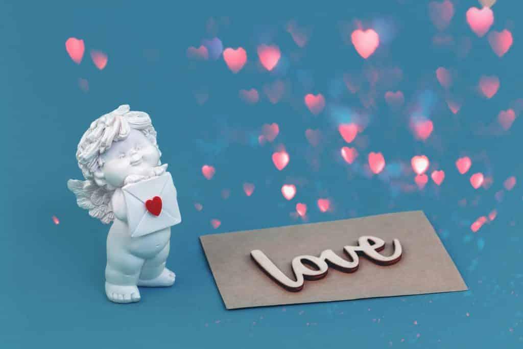 Imagem de fundo azul e sobre ela vários corações na cor rosa. Ao lado uma estátua de um anjinho segurando um envelope na mão com um coração vermelho. Ao lado um papel cinza onde está escrito a palavra Love - amor em inglês.