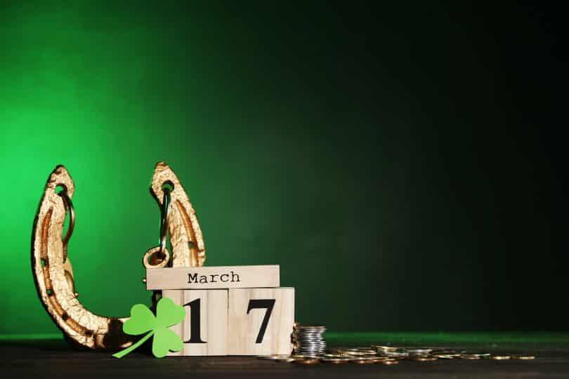 Imagem de fundo verde com um caléndário marcando a data de São Patrício, que é dia 17 de março. Ao lado deste calendário feito de maderia um trevo de três folhas na cor verde, uma ferradura dourada e algumas moedas.