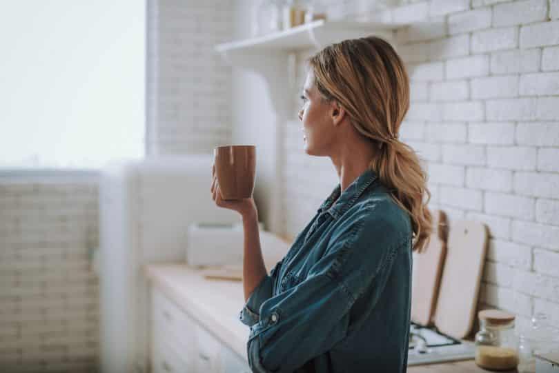 Mulher branca e loira segurando caneca, olhando para janela.