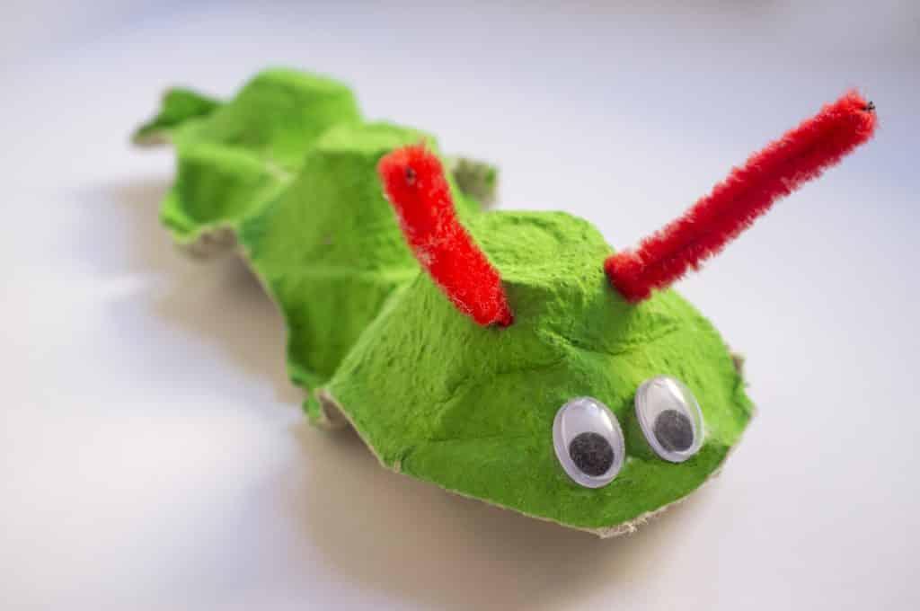 Imagem de um brinquedo reciclado feito de caixa de ovos. É uma cobra na cor verde.