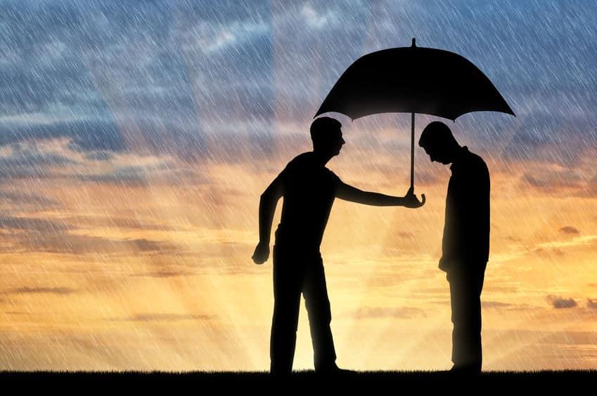 Homem oferecendo guarda-chuva para o outro que não tem
