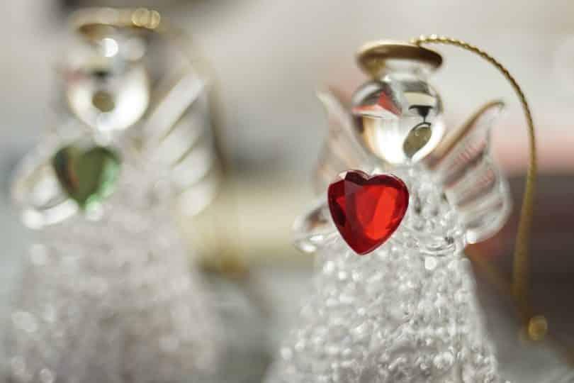 Imagem de dois anjinhos de cristal e ambos seguram um coração um verde e o outro vermelho.