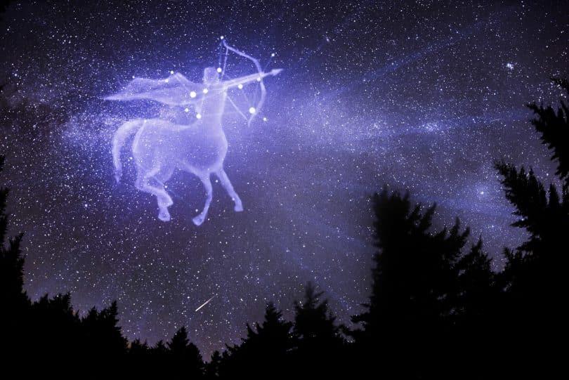 Imagem do céu estrelado com alguns pinheiros ao redor. Ao fundo, o desenho do signo de sagitário.