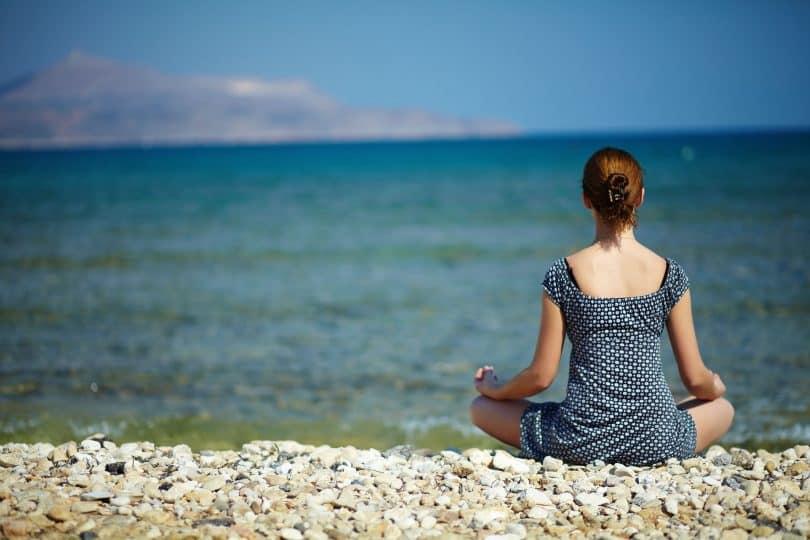 Mulher jovem sentada na praia desfrutando de um momento de paz
