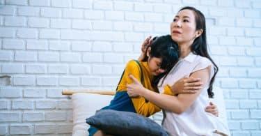 Mãe e filha asiáticas abraçadas num sofá.