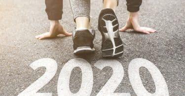 Pés de corredor à frente do número 2020 em asfalto.