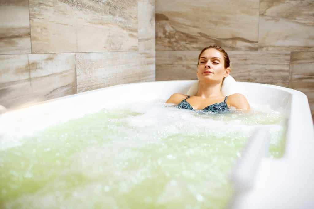 Imagem de uma jovem mulher dentro de uma banheira relaxando.