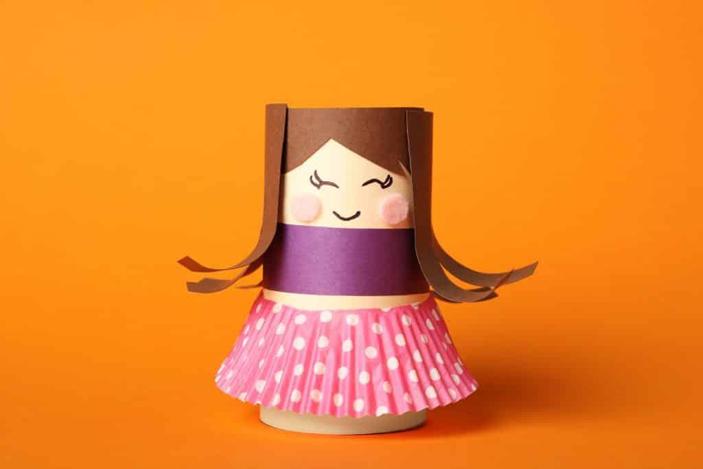 Imagem de um brinquedo reciclado feito de rolo de papel higiênico. É uma bonequinha bem colorida usando uma sainha rosa de bolinha branca.
