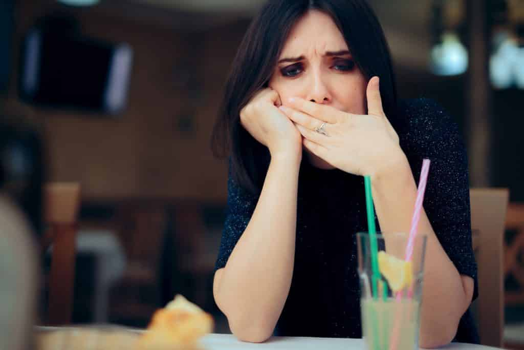 Mulher branca com expressão dolorosa e mão na boca.