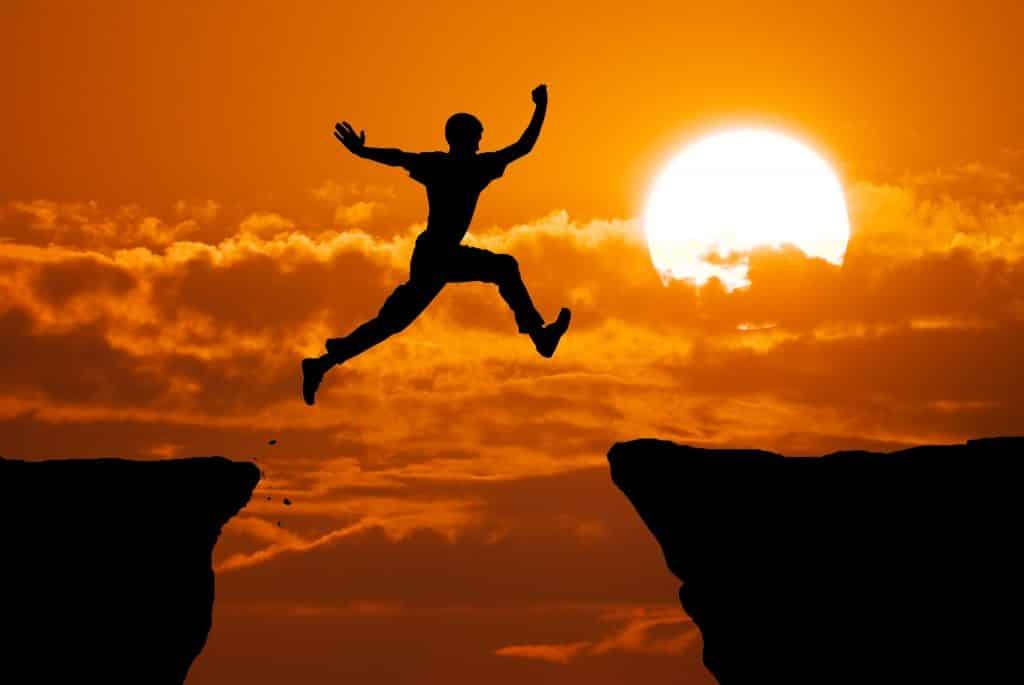 Imagem da silhueta de um homem saltando de uma pedra para a outra em um penhasco. Ao fundo a imagem do Sol.