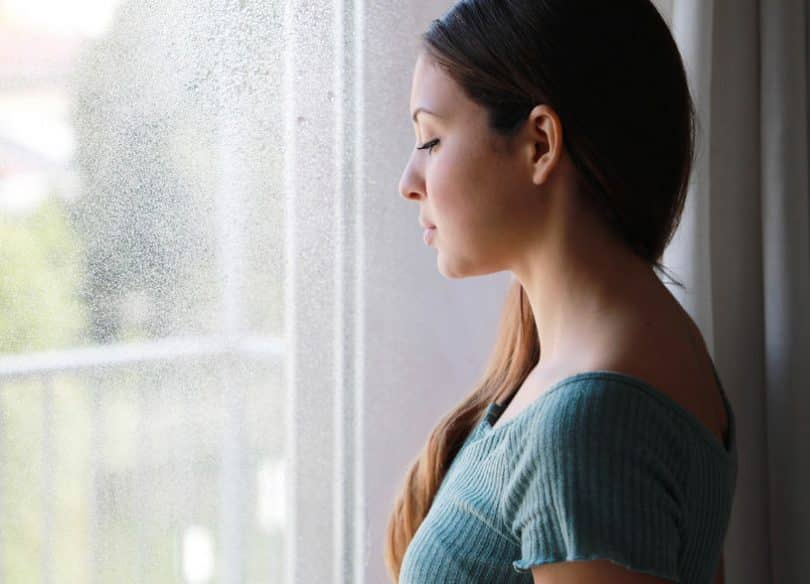 Mulher olhando pela janela, refletindo