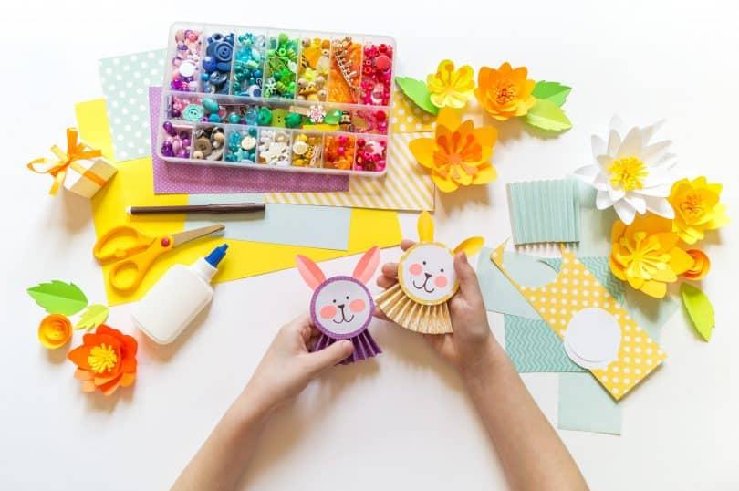 Imagem de uma mesa com vários itens para a fabricação de brinquedos recicláveis. A mão de uma criança segura dois bonecos já prontos.