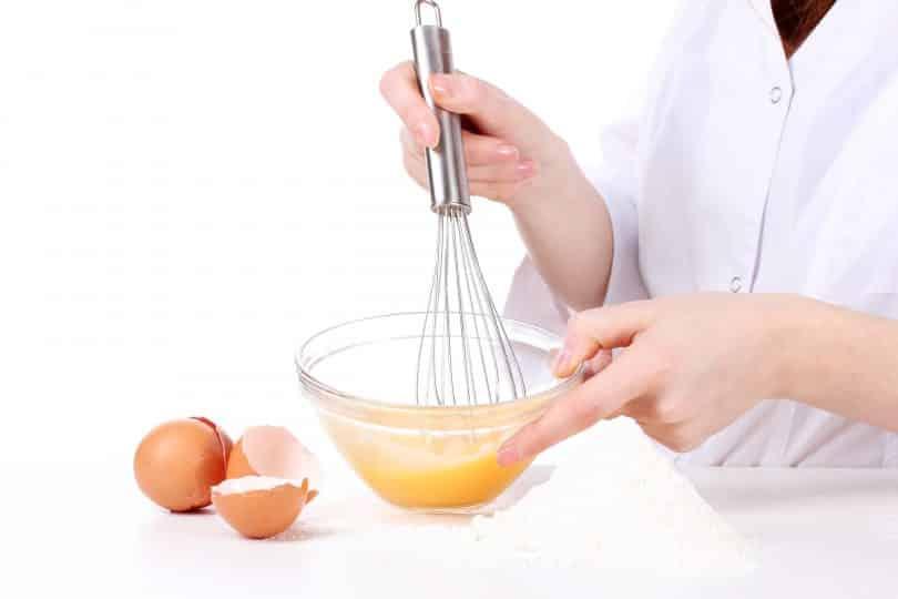 Imagem das mãos de uma mulher mexendo os ovos em uma tigela de vidro. Ela está preparando uma hidratação para os cabelos feita com ovos.