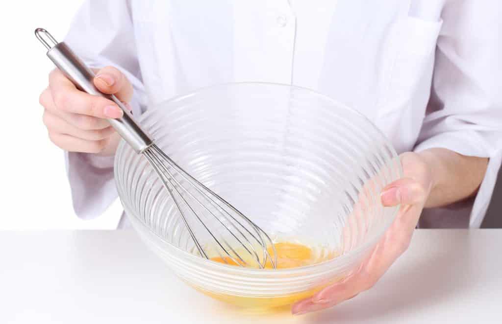 Imagem de uma mulher batendo os ovos em uma tigela de vidro para fazer uma hidratação para os cabelos feita com ovo e banana.