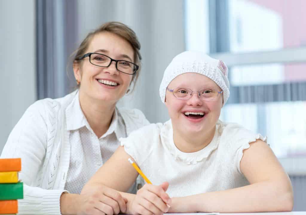 Imagem de uma criança portadora da síndrome de down em uma sala de aula. Ela está ao lado da sua professora. Ela segura um lápis de cor amarela. Ambas usam óculos de grau e roupas brancas e estão sorrindo.
