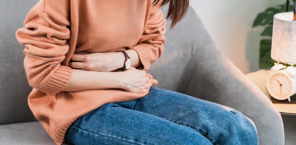 Mulher sentada com a mão no ventre.