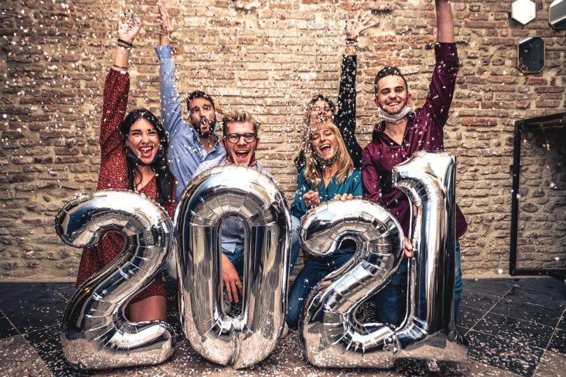 Pessoas Sorridentes com balões prateados celebrando o Ano Novo com máscara facial abaixada na época do coronavírus