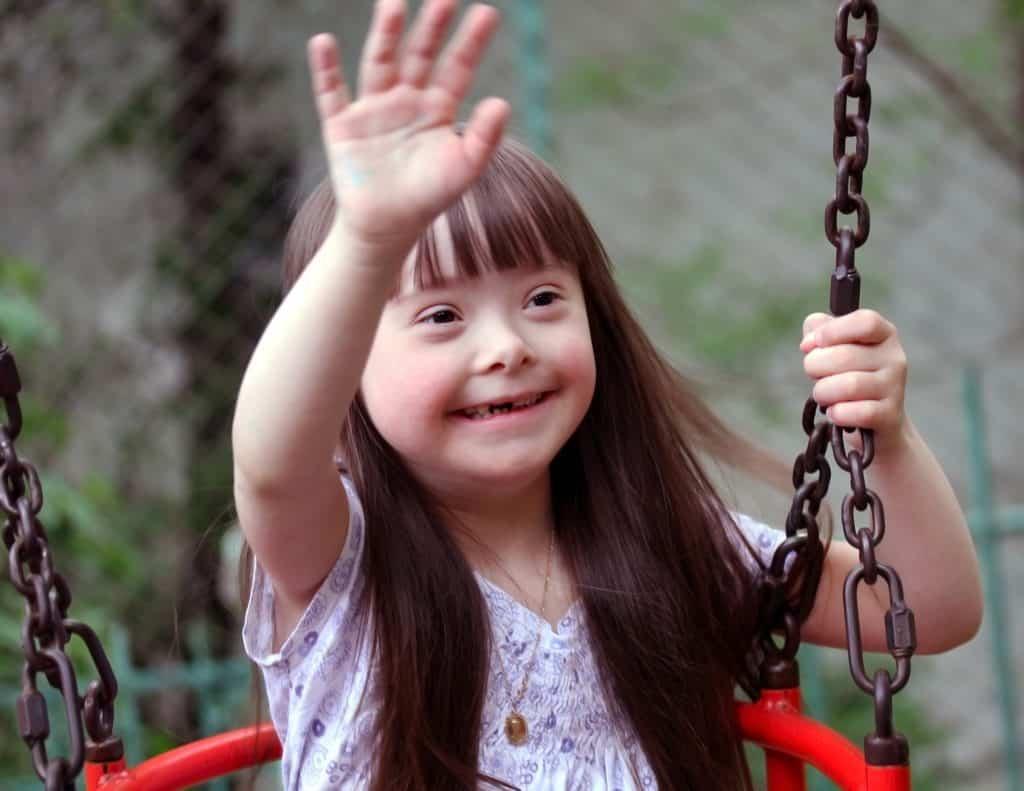 Imagem de uma criança portadora da síndrome de down. Ela está sentada em um balanço na hora do intervalo na escola.