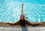 Imagem de uma piscina com uma água azul e limpa. Dentro dela uma mulher encostada na beirada relaxando as suas pernas.
