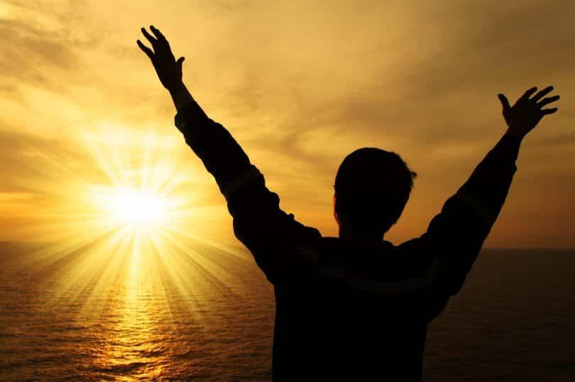 Imagem da silhueta masculina olhando para a luz do sol que brilha no horizonte sobre o oceano.