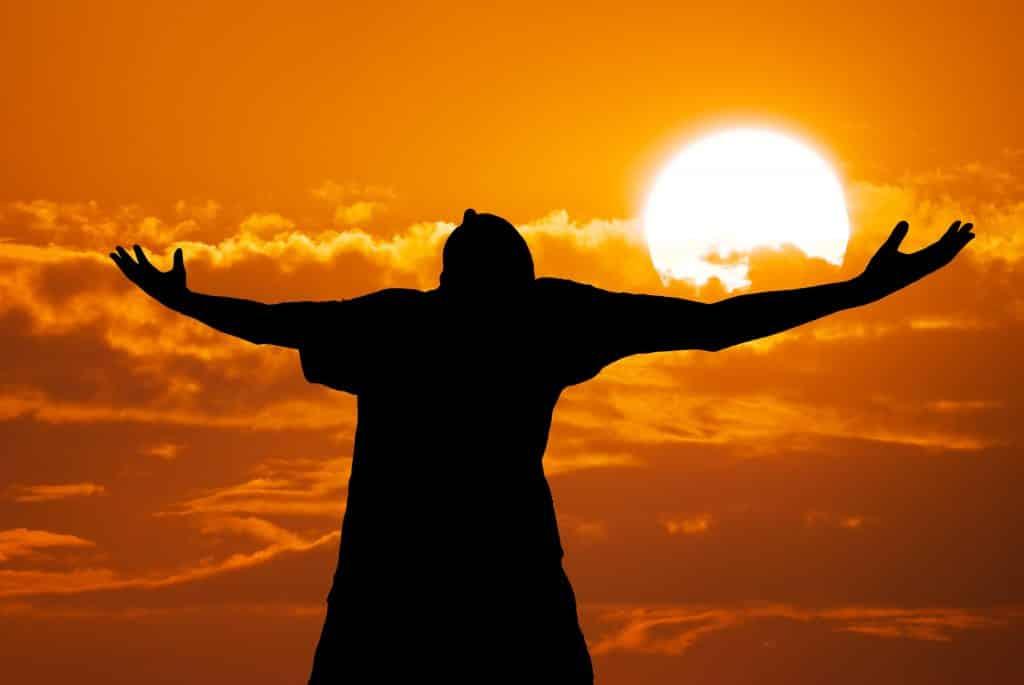 Imagem da silhueta de um homem de braços abertos e ao fundo a imagem do sol brilhando no horizonte.
