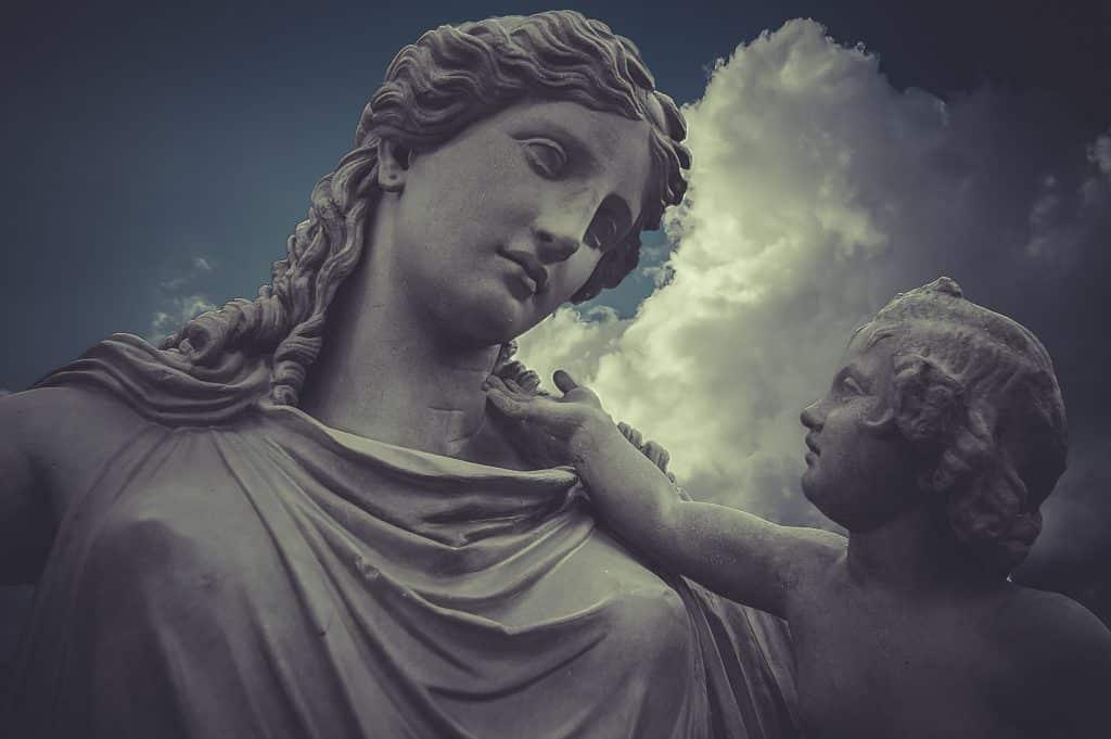 Imagem da estátua de uma mulher representando a deusa Hera e ao lado dela uma criança.
