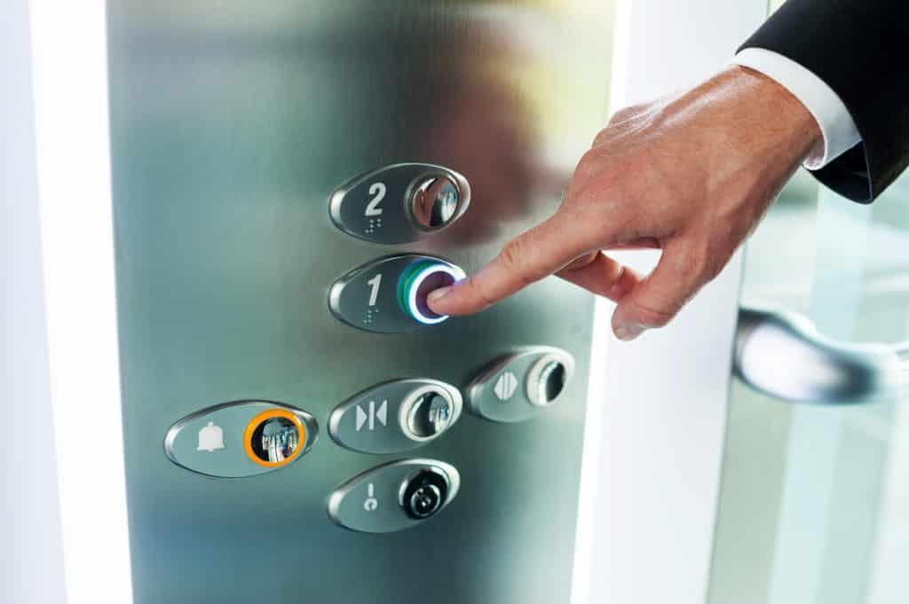 Imagem interna do elevador e uma mão masculina apertando o primeiro andar do painel.