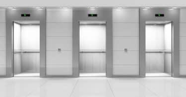 Imagem do hall de um prédio e de três elevadores com as portas abertas.