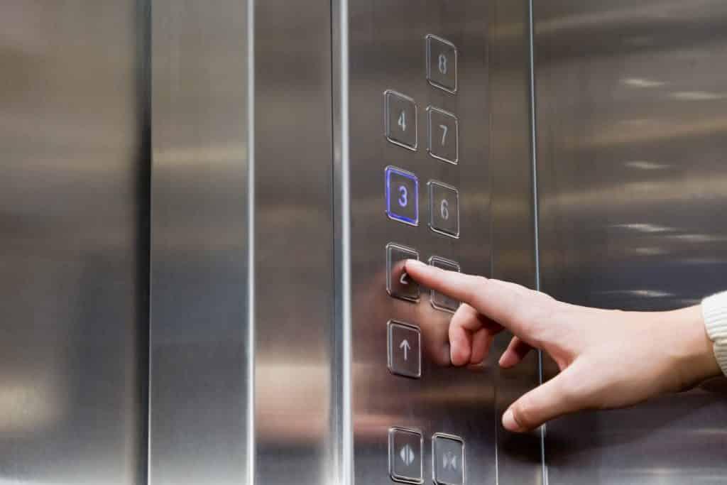 Imagem interna de um elevador e a mão de uma mulher apertado o número 2 do painel indicativo dos andares.